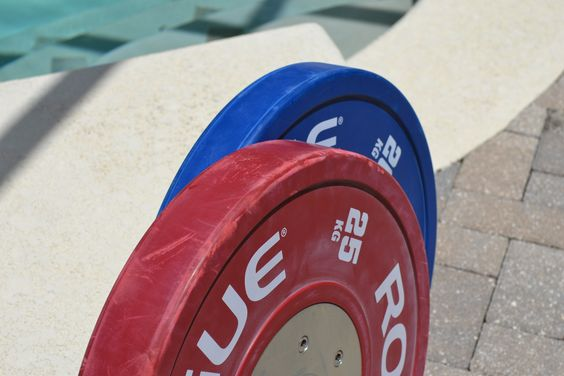 Bumper plates are wider than iron plates and have no lip.  Moving them around is a better grip workout.