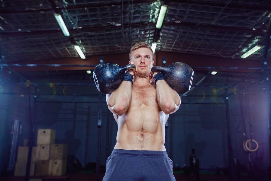 """Man holding two kettlebells in the """"rack"""" position."""