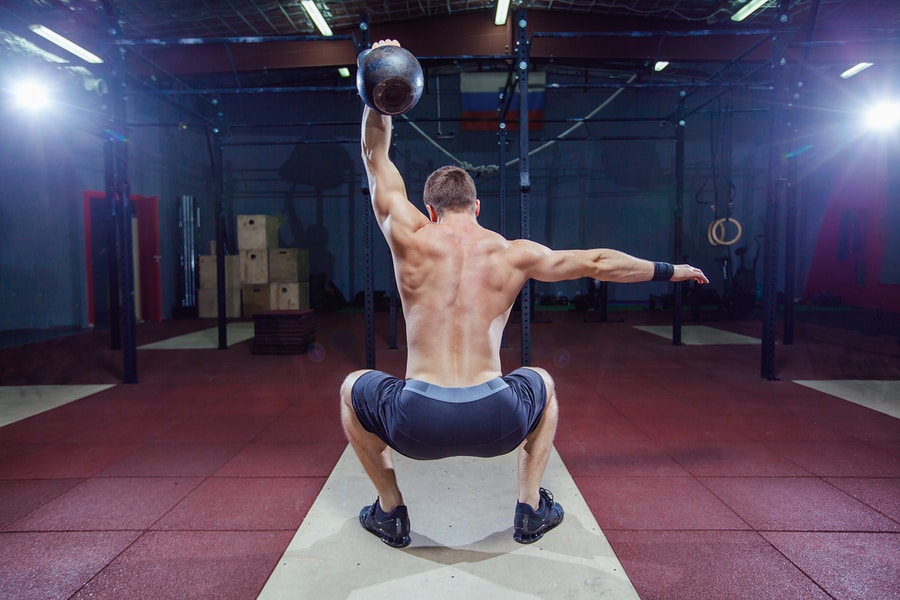 Man using a kettlebell to workout in a gym