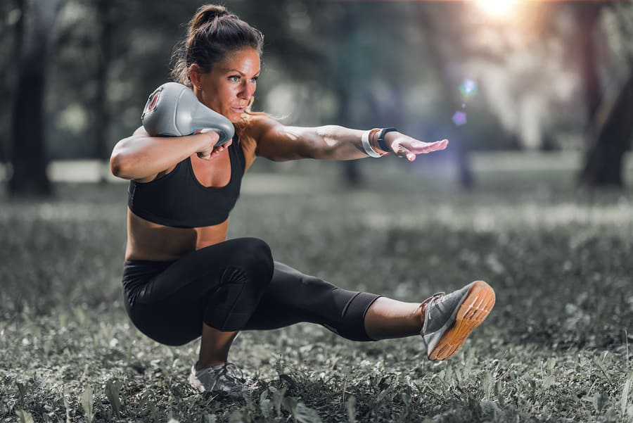 Woman performing a pistol squat with a kettlebell in the rack position for extra resistance