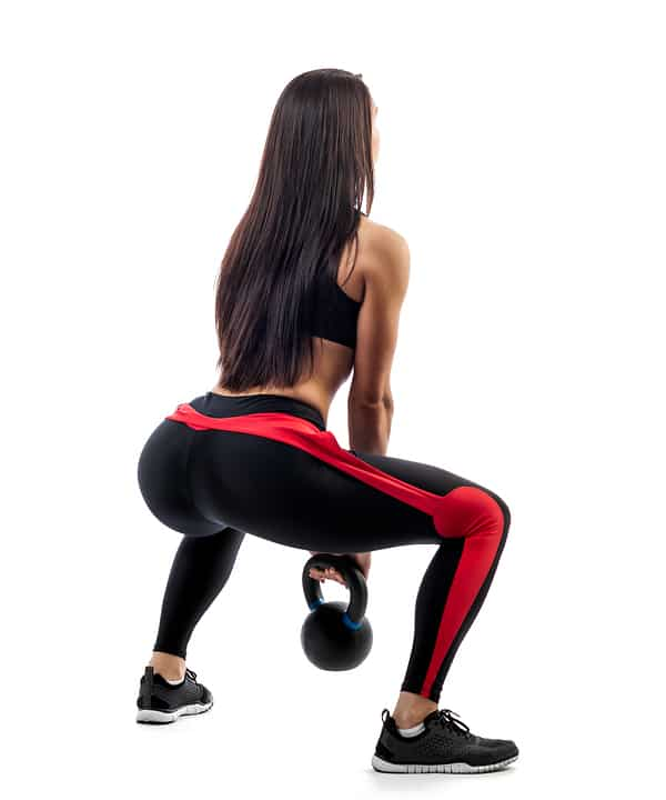 Woman picking up a kettlebell from the floor - with excellent form.