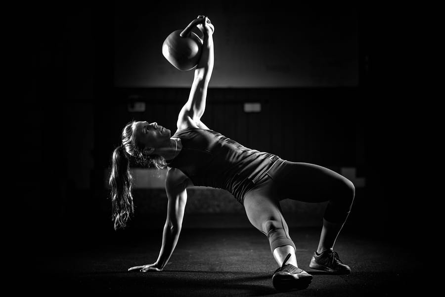"""Fit woman using a kettlebell as part of a """"Turkish Get Up"""""""