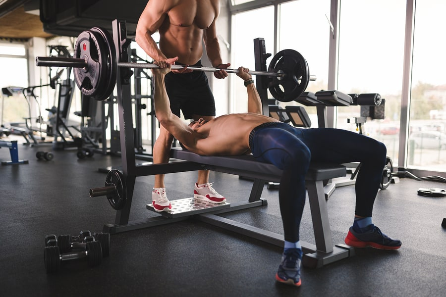 Two men performing the bench press in the gym