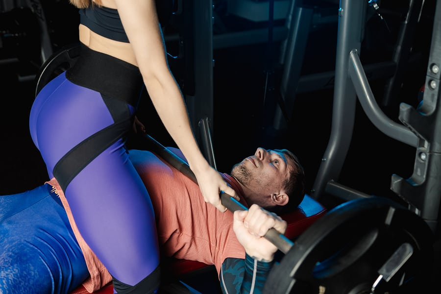 a woman assisting a man with bench pressing in the gym.