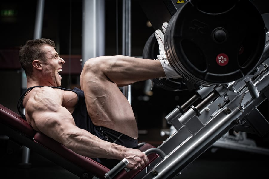 The leg press machine in use at the gym by a bodybuilder