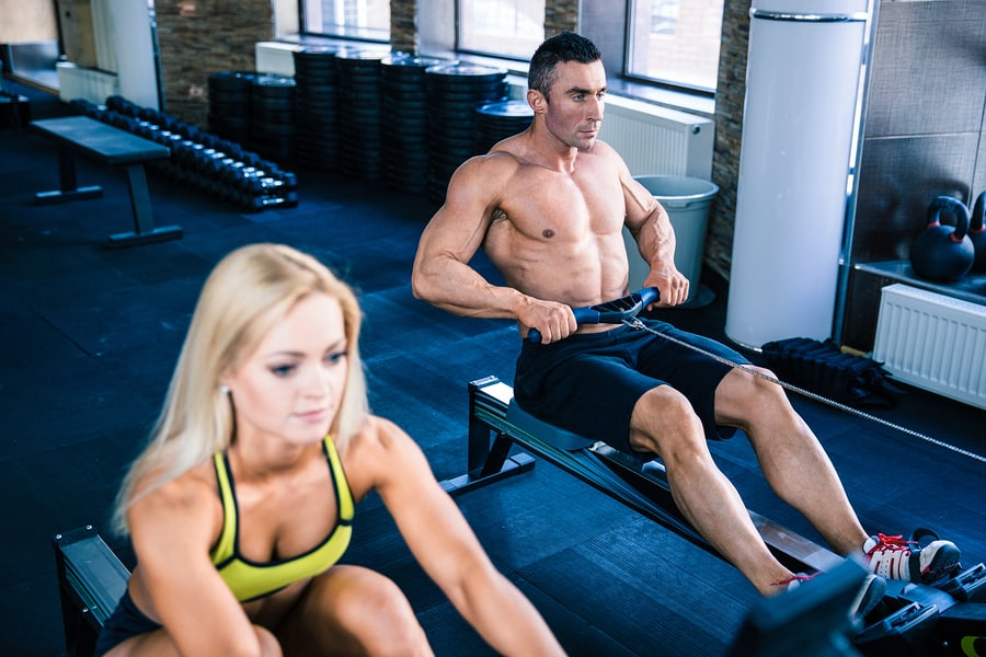 Couple on rowers in the gym