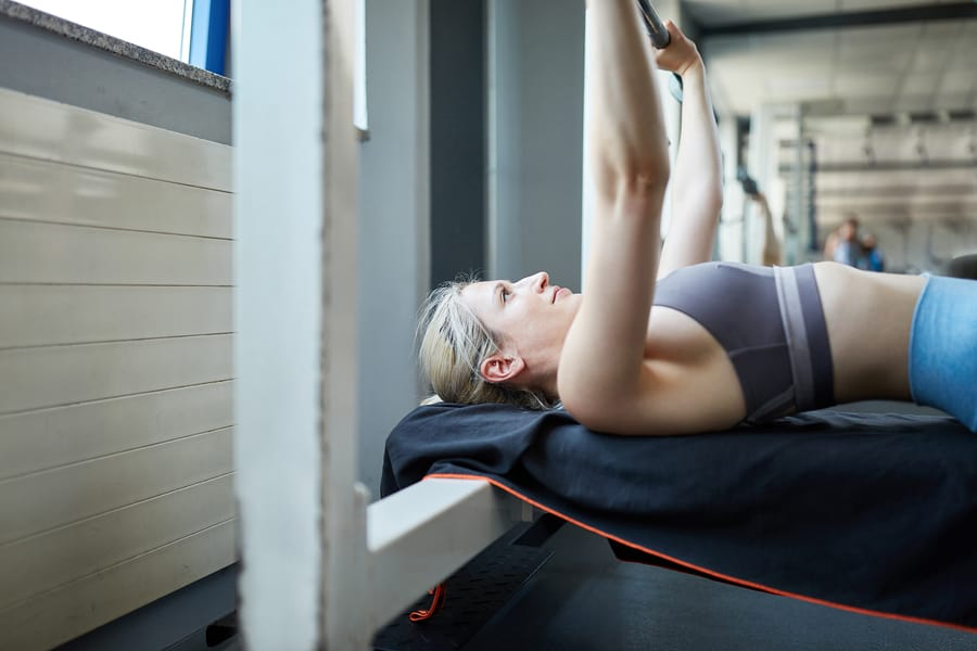 A woman performing the bench press on an bench with an olympic barbell