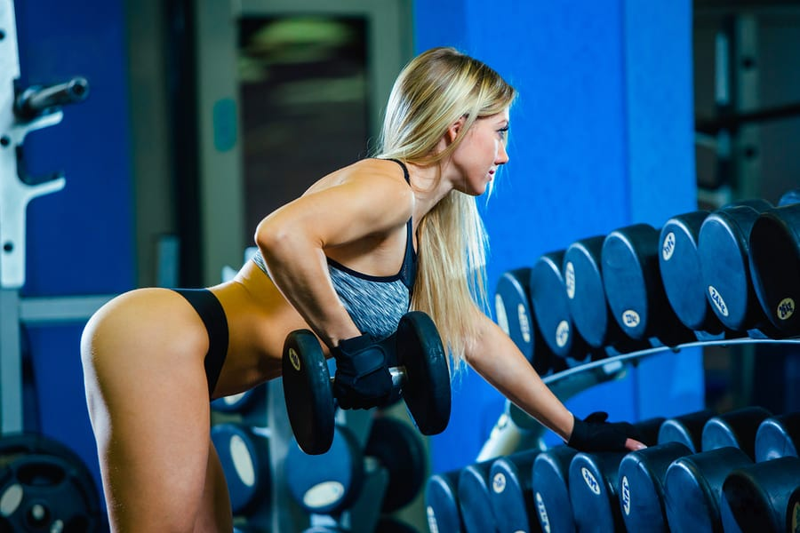 Woman performing dumbbell rows in the gym