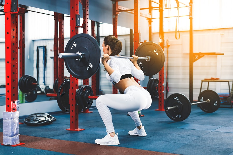 Woman performing barbell back squat in the gym