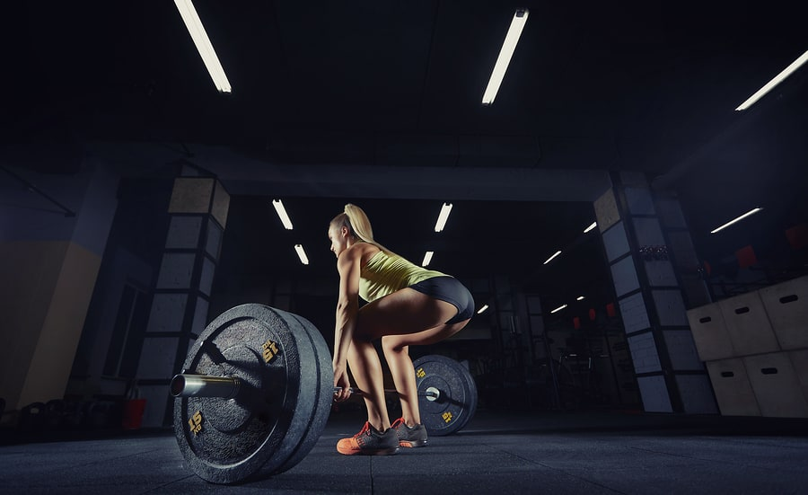 Woman performing deadlifts in the gym