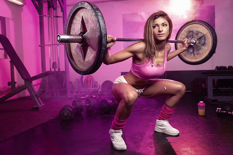 Woman in a garage gym doing squats