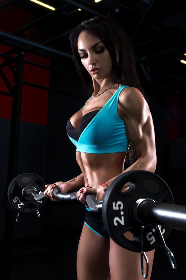 sexy brunette performs curls at the gym