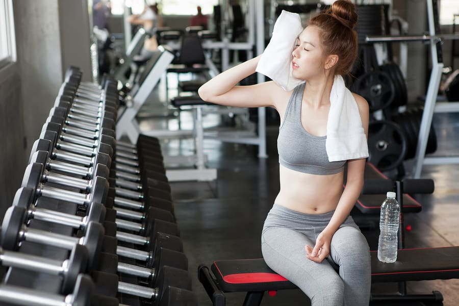 Young woman using a towel to wipe off sweat in the gym