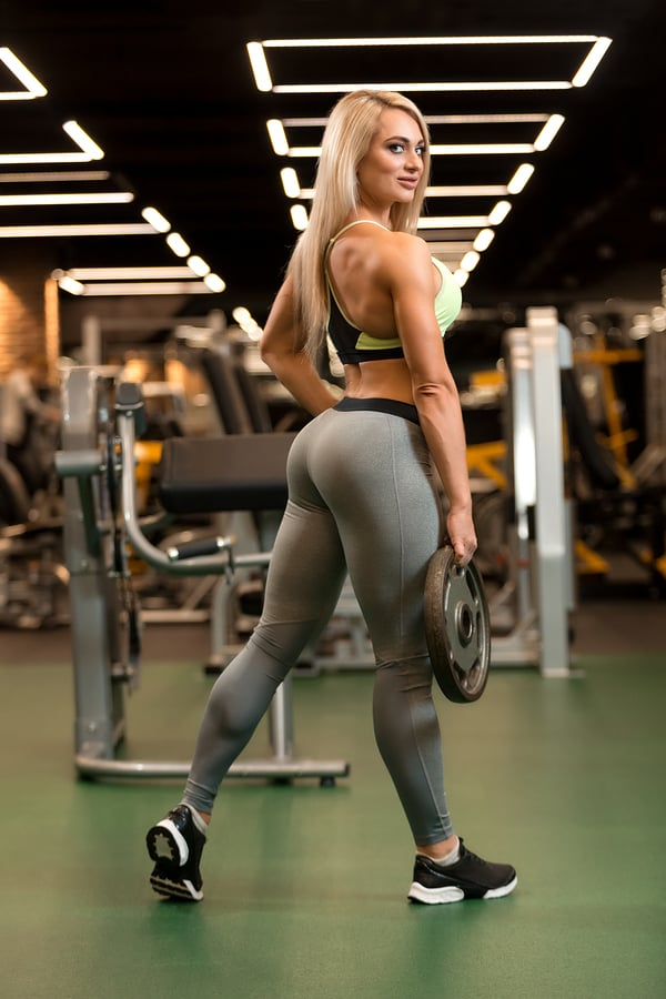 Sexy woman with weight plates in the gym