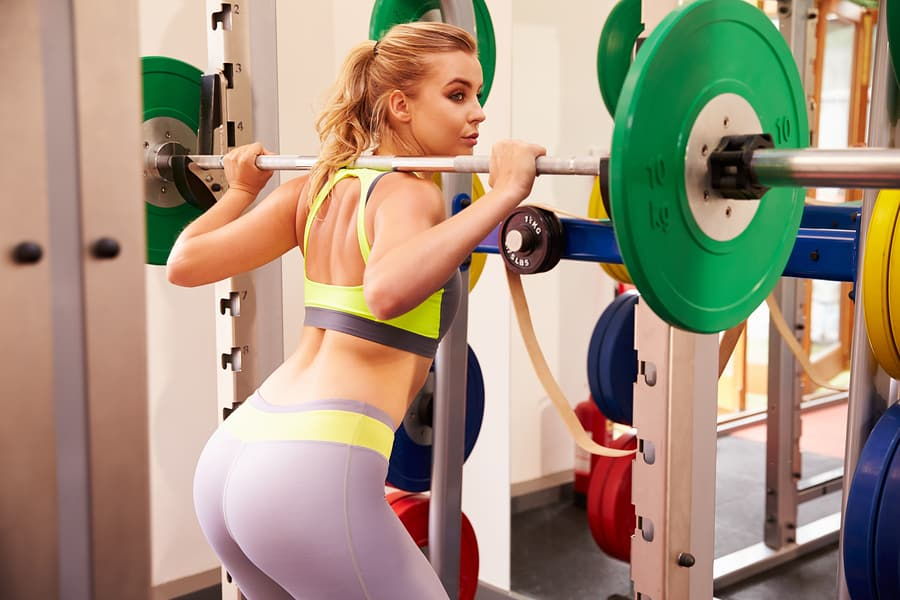 Young woman squatting in a power rack with a barbell