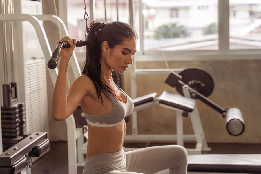 sexy woman using a lat pulldown machine at a gym